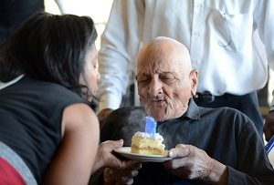With a little help from daughter Delane Sims, Andrew Hatch blows out candles on his cake as he celebrates his 115th birthday in Oakland, Calif., on Monday, Oct. 7, 2013. (Kristopher Skinner/Bay Area News Group)